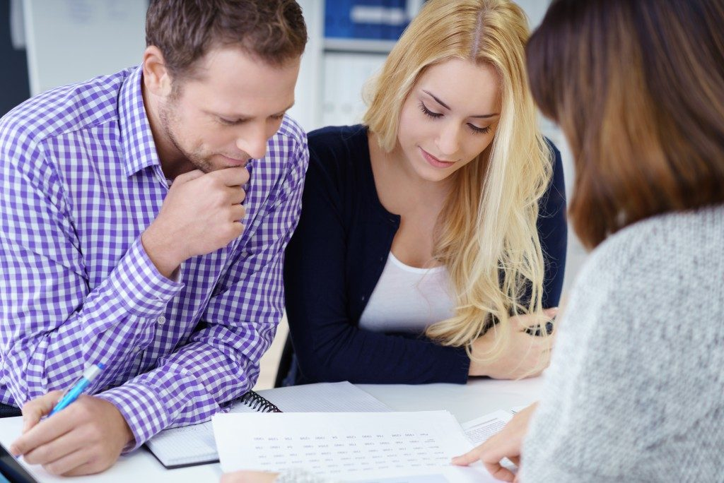 couple reading document presented by the real estate agent