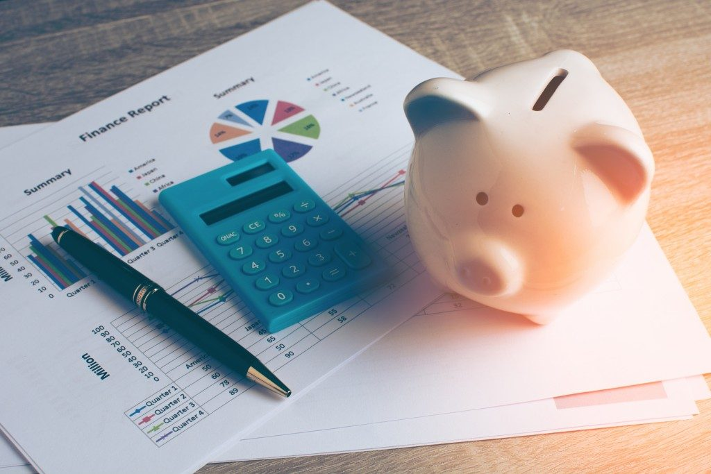saving money concept with piggy bank, calculator and graphs