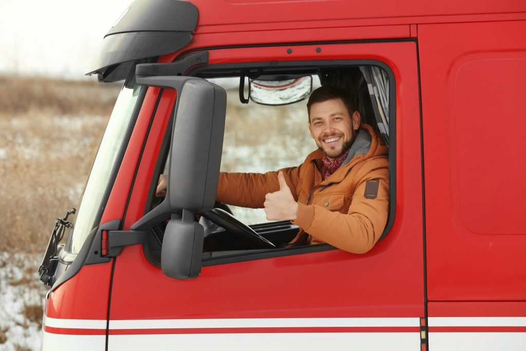 trucker driving a red freight truck