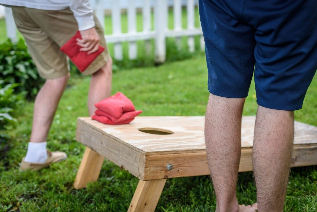 Two guys playing Cornhole game
