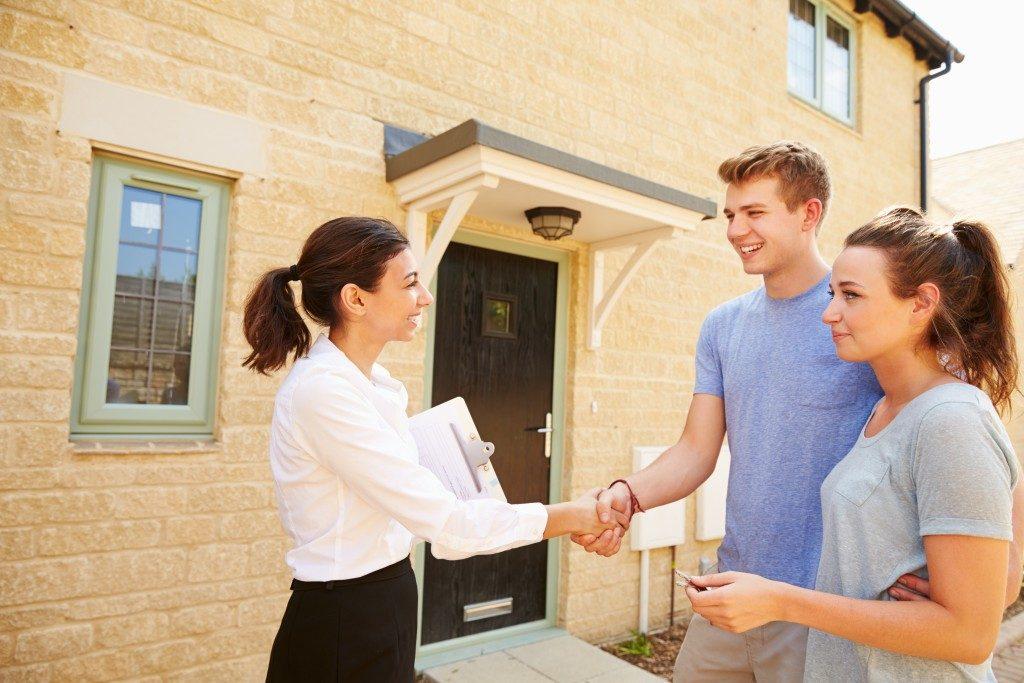 Couple shaking hand of broker