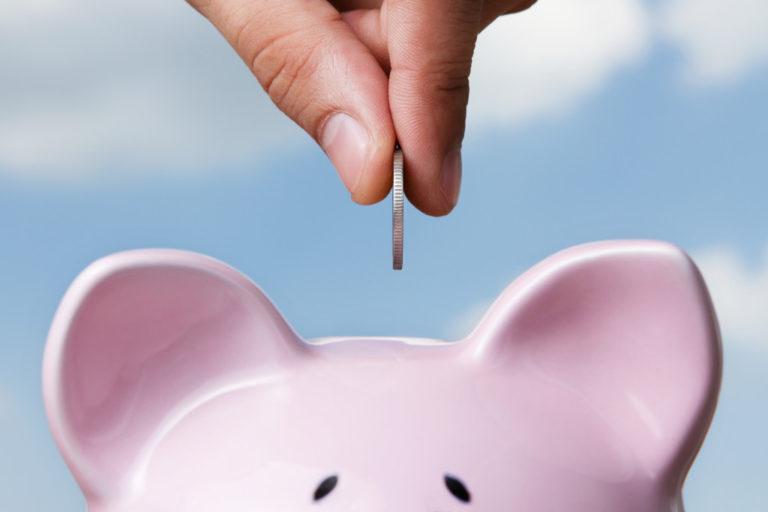 putting coin inside piggy bank
