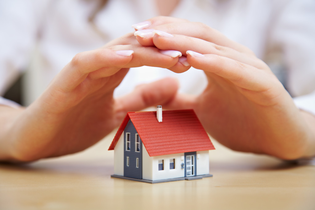 woman covering miniature house