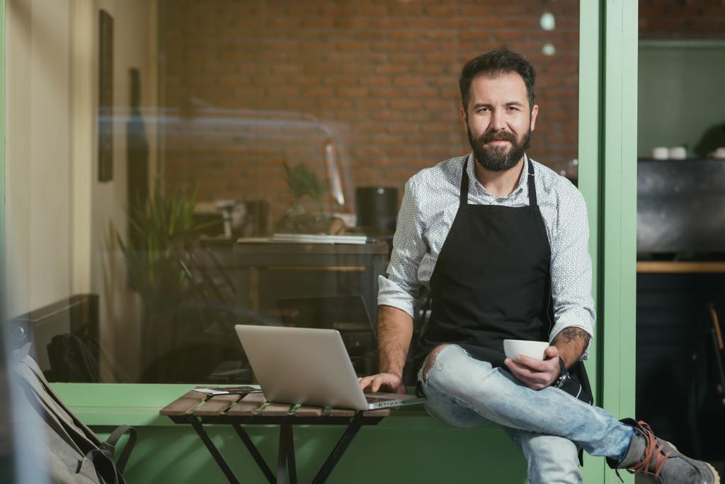 Barista typing on laptop